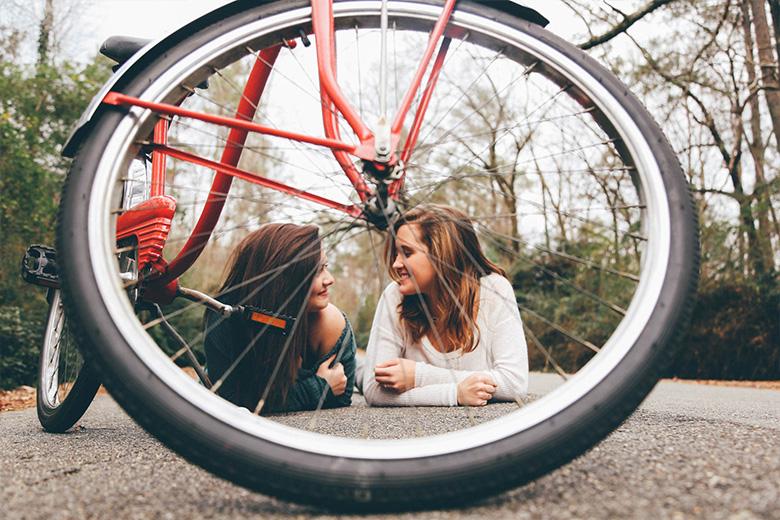 2 נשים מול אופניים חשמליות מחייכות אחת לשניה