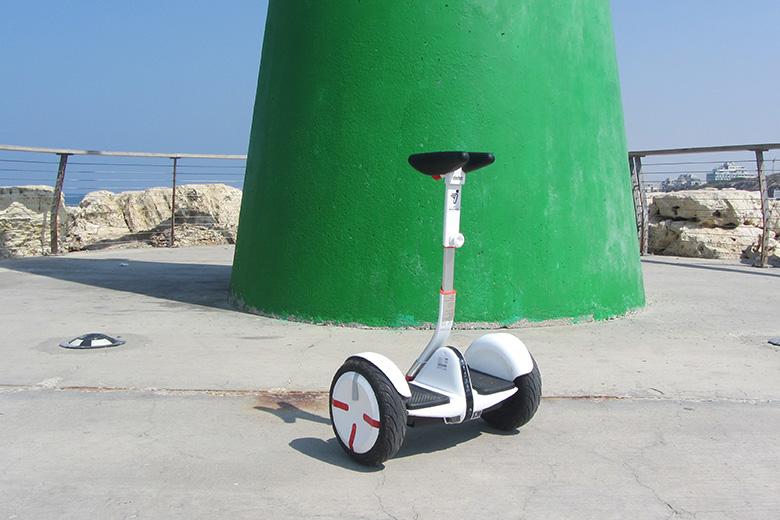 סגווי מיני פרו לבן על רקע מגדל אור ירוק